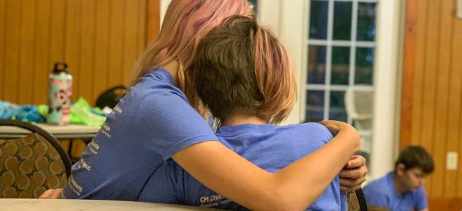 Two 12-year-olds comfort each other while sharing stories about their families. Some say it's only at camp that they don't feel alone because they meet other children in their situation. Some children have seen their parents overdose and some have had to call 911. Many have been taken away to foster care multiple times.  Courtesy of Jared Case